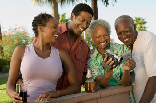 Family Looking at Video Camera at Barbecue
